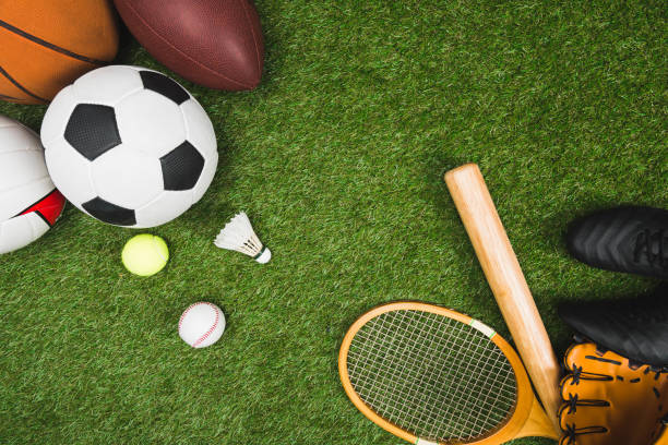 top view of various sport balls, baseball bat and glove, badminton racket on green lawn stock photo