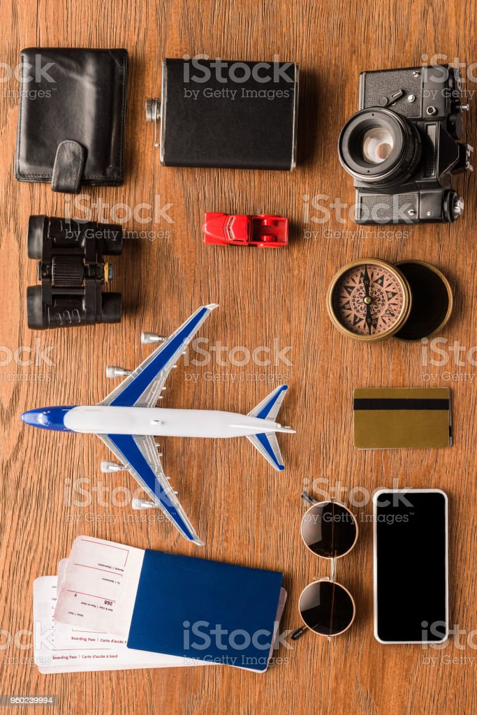 top view of various travel attributes on wooden surface stock photo