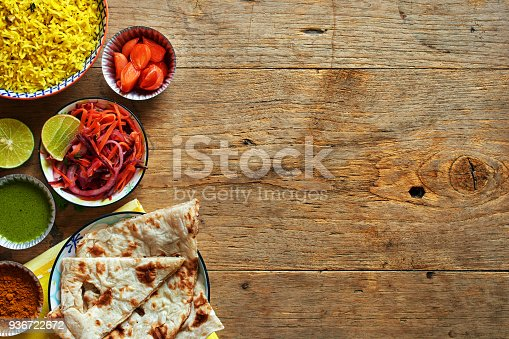 istock Top view of vegetarian indian dishes on wooden table with copy space. 936722672
