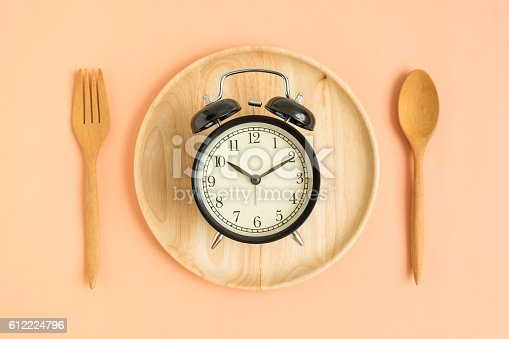 1139289535 istock photo Top view of vintage clock on wooden plate 612224796