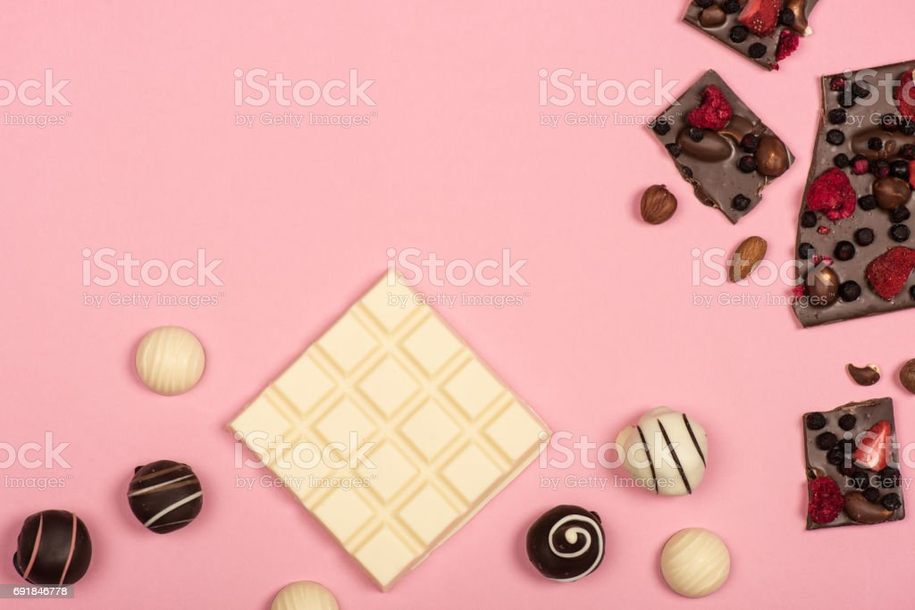 Top view of white chocolate, chocolate with nuts and fruits and sweet candies isolated on pink stock photo