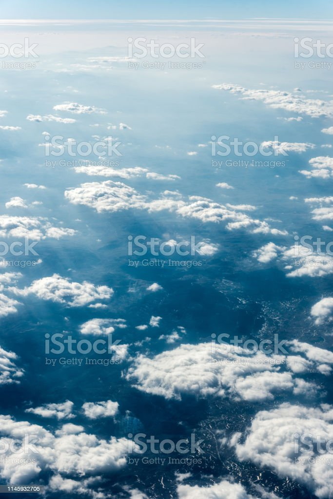 Top view of white clouds above the ground or water. Vertical frame