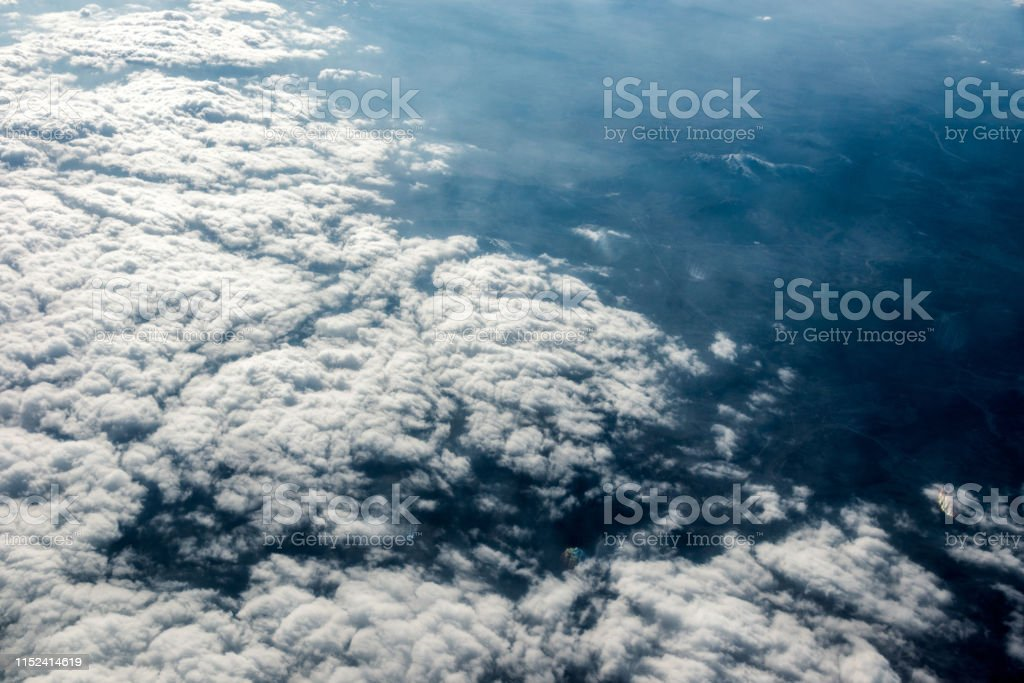 Top view of white clouds above the ground or water. Horizontal frame