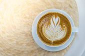 Top view of white cup of hot coffee latte with milk foam heart shape art on round table and copy space.