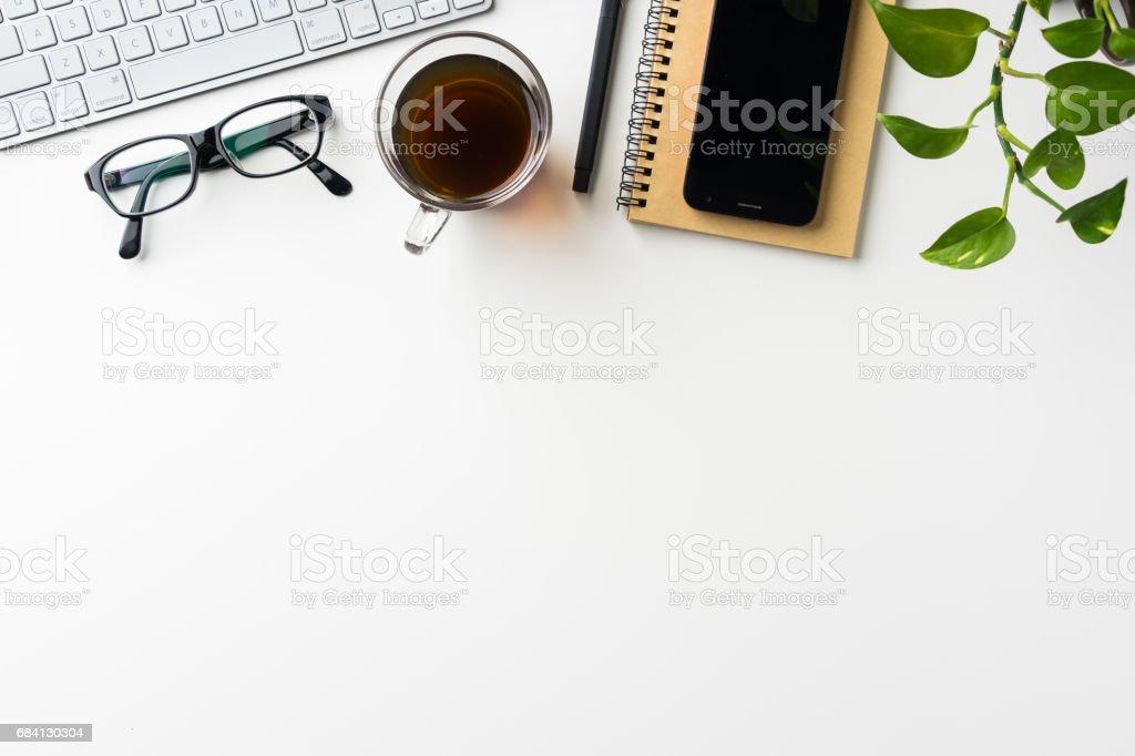 Bovenaanzicht van de witte achtergrond van het bureaublad met laptop, koffie, slimme telefoon... royalty free stockfoto