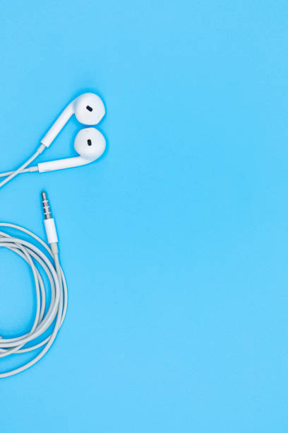 Top view of White Earphones on Blue plastic texture background. Pastel color concept, Minimal concept. Copy space. Music is my life concept stock photo