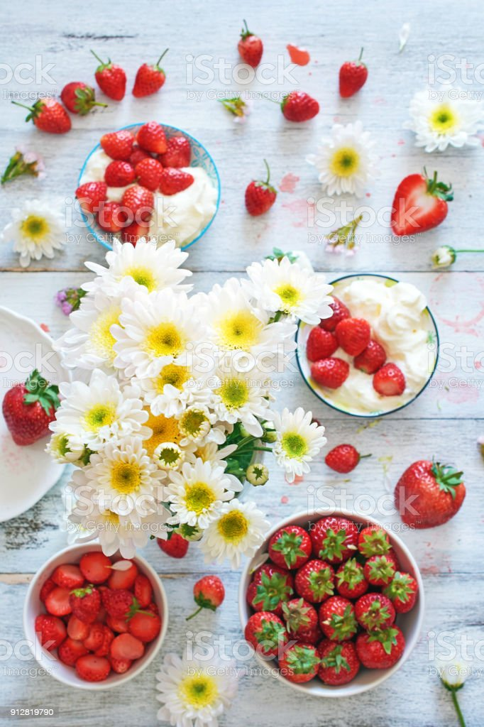 Flowers with strawberry on the table. Feminine background concept.