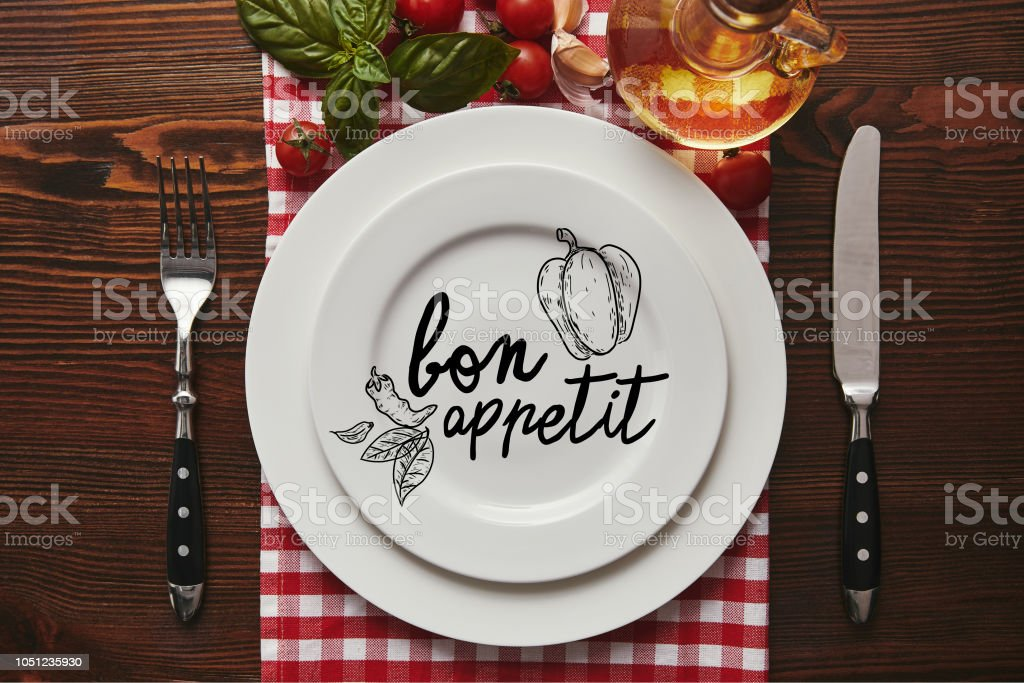 top view of white plates with 'bon appetit' lettering, cutlery and fresh basil with tomatoes and oil on wooden surface stock photo