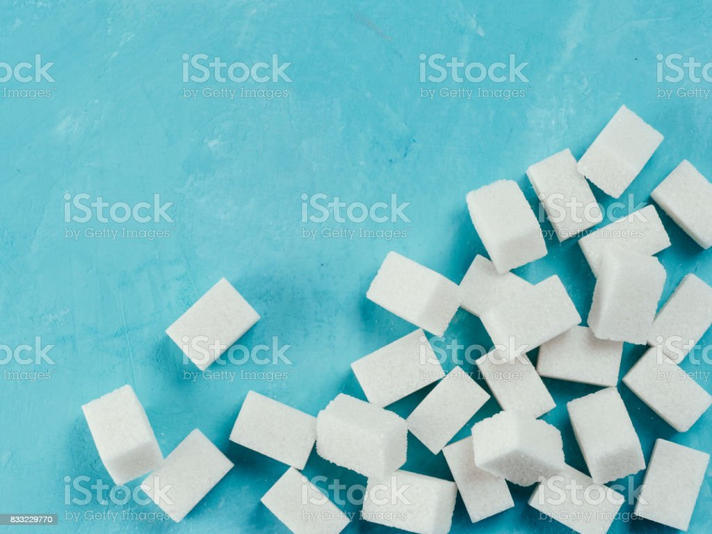 Top view of white sugar cubes on blue concrete background stock photo