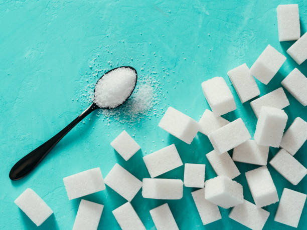 Top view of white sugar cubes on turquoise background stock photo
