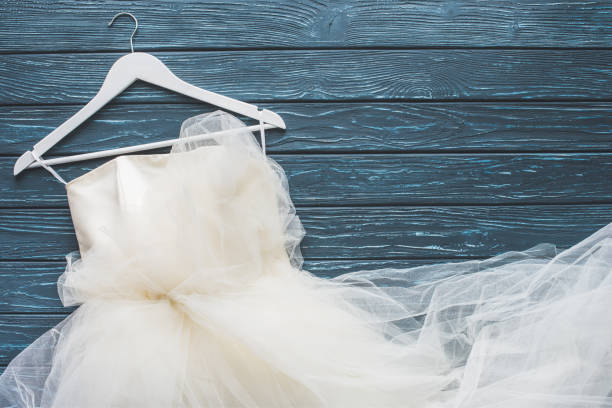 top view of white wedding dress on hanger on wooden dark blue tabletop stock photo