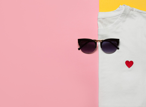 Top view of white woman t-shirt with sunglasses on pink and yellow background. Fashion clothes set. Flat lay. Place for text. 90's style