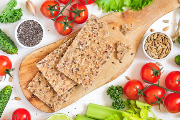Top view of whole grain rye crispbreads on a wooden serving board surrounded fresh vegetables, greens and seeds over white background. stock photo