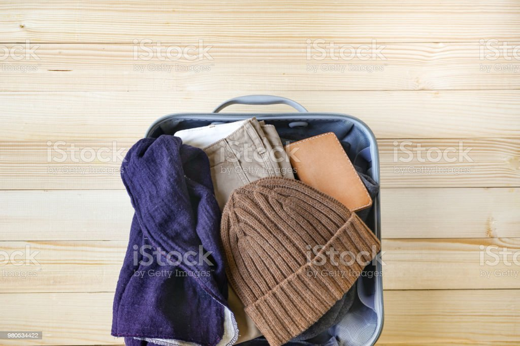 6950938b9c6 Top view of winter outfit and accessories with open suitcase on wood  background