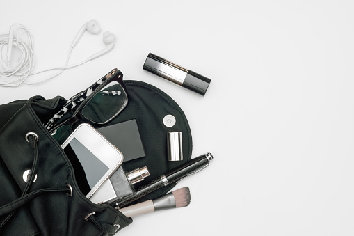 istock Top view of woman black bag open out with accessories smartphone, perfume, pens, cosmetics, earphone and glasses  on white background 1080909974