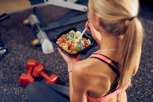 Top view of woman eating healthy food while sitting in a gym. stock photo