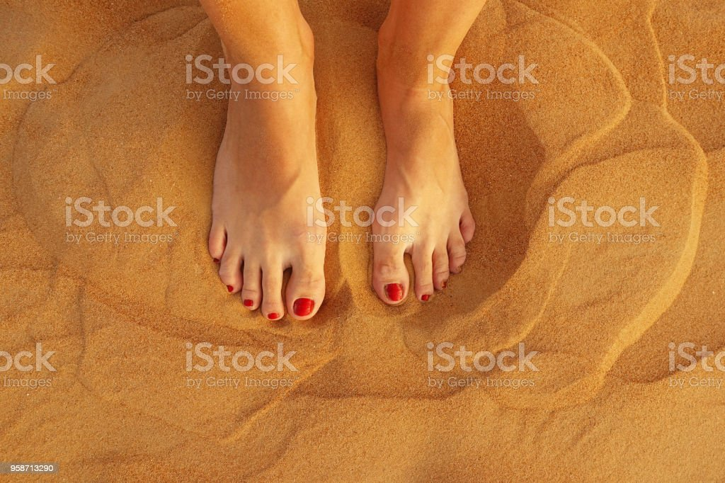 Top view of woman feet in golden desert sand stock photo