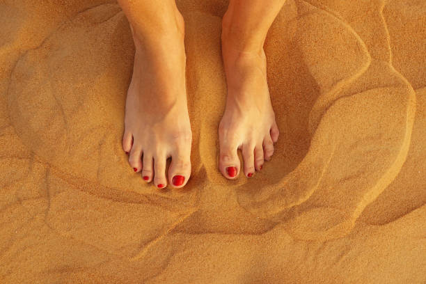 Top view of woman feet in golden desert sand stock photo