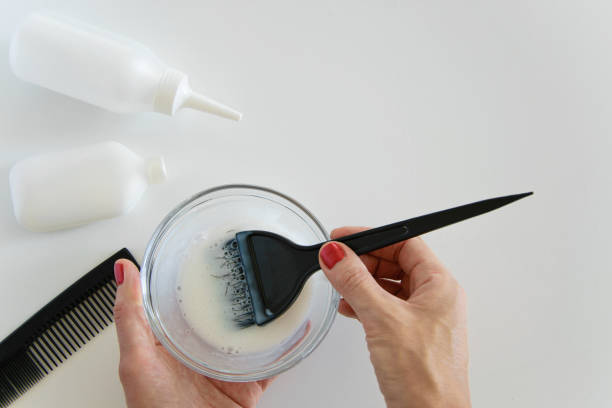top view of woman hand mixing hair dye color and dye hair products on white background, space for text - barwnik zdjęcia i obrazy z banku zdjęć