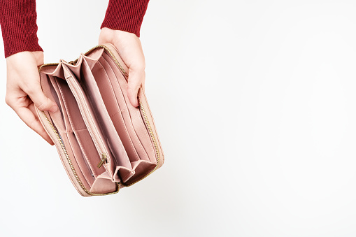 1018458132 istock photo Top view of woman hands holding open empty wallet. Bankruptcy. Unemployment. No cash in leather pocket. Lack of money concept. Mockup style. Isolated on white 1247661305