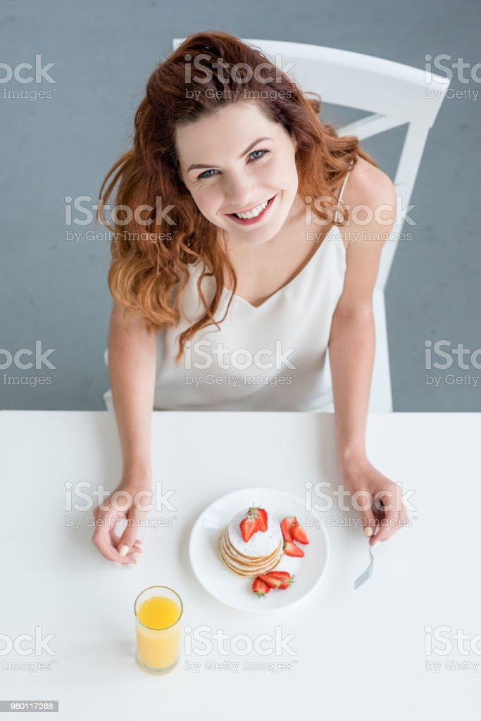 top view of woman having orange juice and pancakes with strawberry for breakfast and looking at camera stock photo