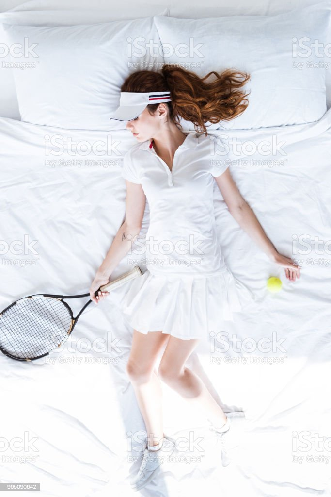 Top view of woman in tennis clothes sleeping on bed with racket and ball royalty-free stock photo