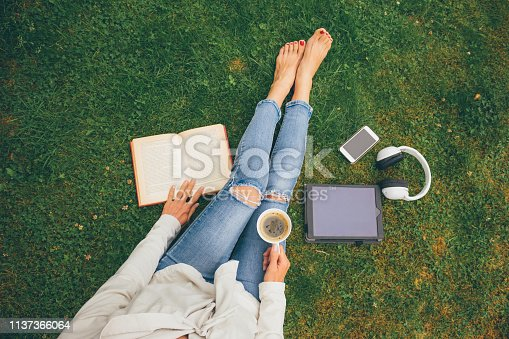 istock Top view of woman sitting in park (garden) on the green grass with smartphone, headphones, tablet, book and coffee in the hand 1137366064