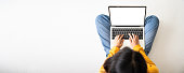 istock Top view of woman sitting on floor and using laptop blank screen white background. Mockup, template for your text, Clipping paths included for device screen. Panoramic image with empty copy space 1278904216