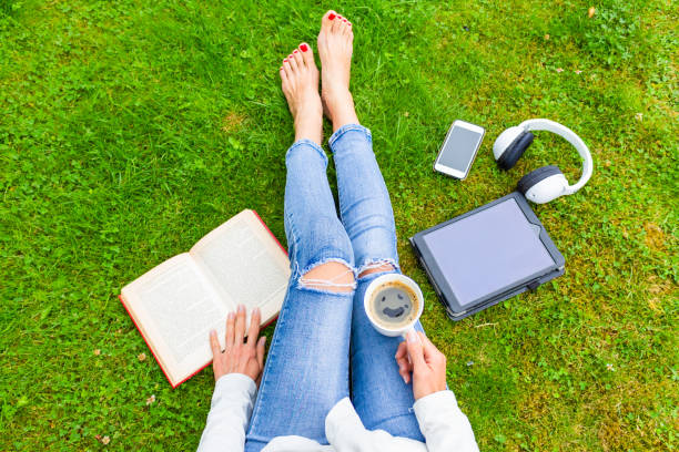 Top view of woman sitting on the green grass, relaxing with smartphone, headphones, tablet, book and coffee (with smile) in the hand