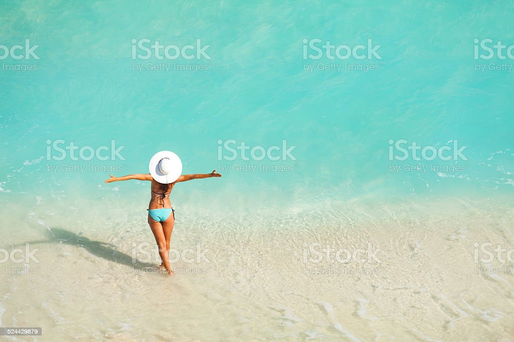 Top view of woman with white hat standing in ocean stock photo