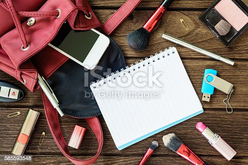 Top view of women bag stuff female accessories on wooden texture background