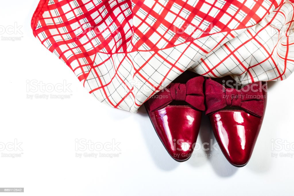 Top view of women's vintage red shoes with bows with red and white plaid scarf, on white background, copy space, stock photo