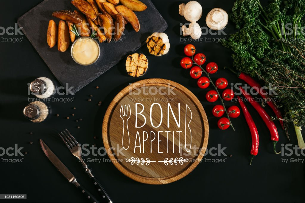 top view of wooden board  with 'bon appetit' lettering, vegetables and baked potatoes on black stock photo