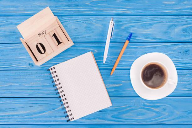 vue de dessus du calendrier en bois avec la date du 1er mai, tasse à café, Manuel vide et stylos, notion de jour de travailleurs internationaux - Photo