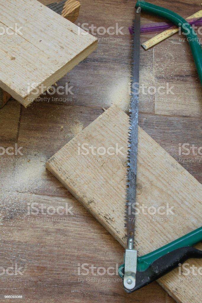 Ovanifrån av träslöjd verktyg - saw och planka - Royaltyfri Akademikeryrke Bildbanksbilder