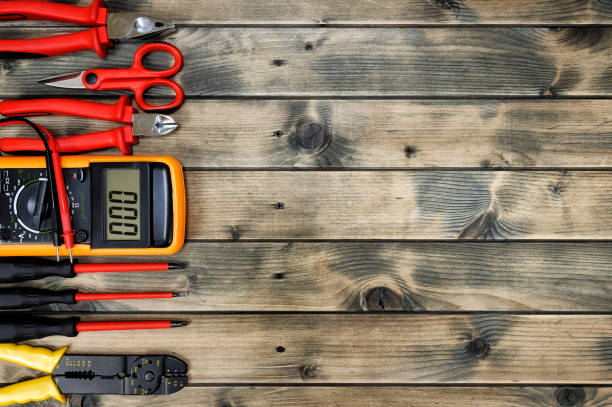 Top view of work tools for residential electrical installation on antique wooden background. stock photo