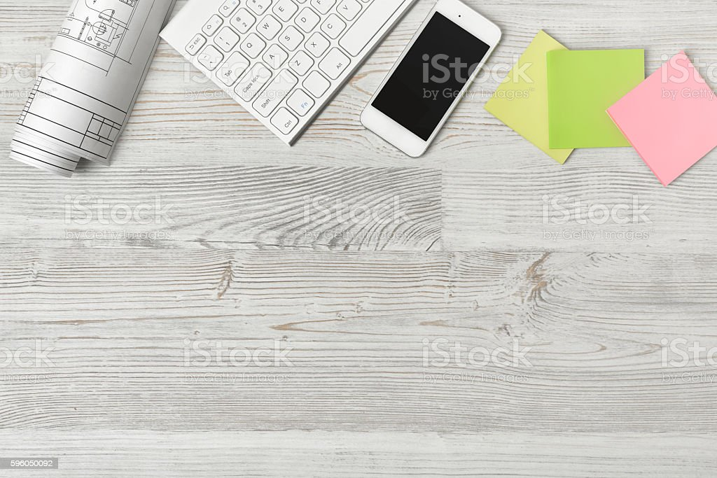 Top view of workplace with paper roll, keyboard, smartphone and royalty-free stock photo