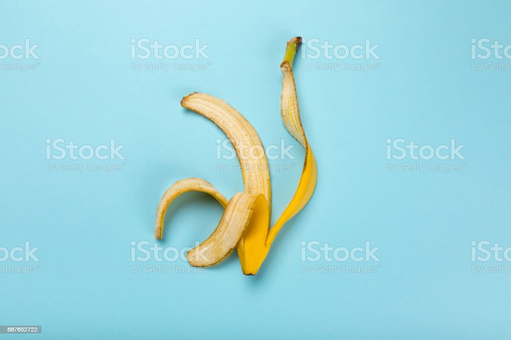 Top view of yellow banana peel isolated on blue, colorful background stock photo