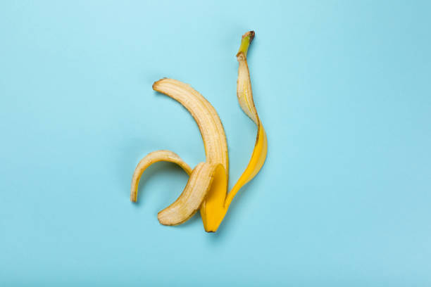 Top view of yellow banana peel isolated on blue, colorful background Top view of yellow banana peel isolated on blue, colorful background banana peel stock pictures, royalty-free photos & images