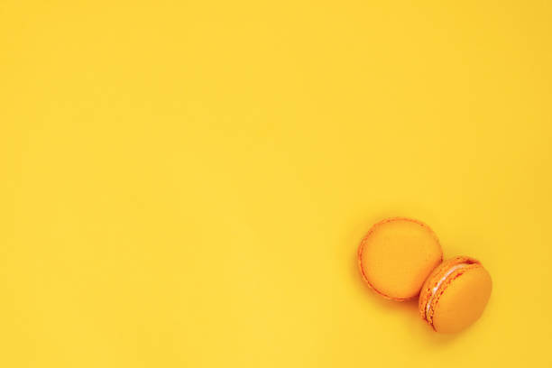 Top view of yellow macaroons over yellow background. Copy space. - foto stock