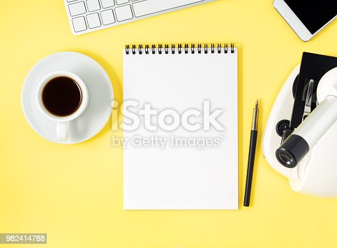 istock Top view of yellow office desktop with microscope, notepad, computer, smartphone. Mock up, empty space, science template 982414788