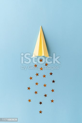 istock Top view of yellow paper plane with golden star shaped confetti trail on blue background. Minimalist flat lay image with copy space. 1171690928