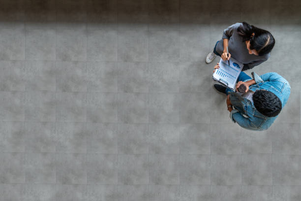 Top view of young asian business team standing, talking and reporting with annual report document in modern workplace. Above view of casual creative team discussion with report performance. stock photo