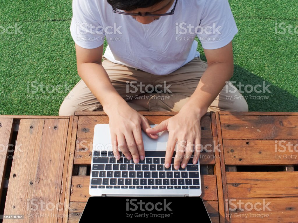 Top view of young Asian man using computer laptop at outdoors. royalty-free stock photo