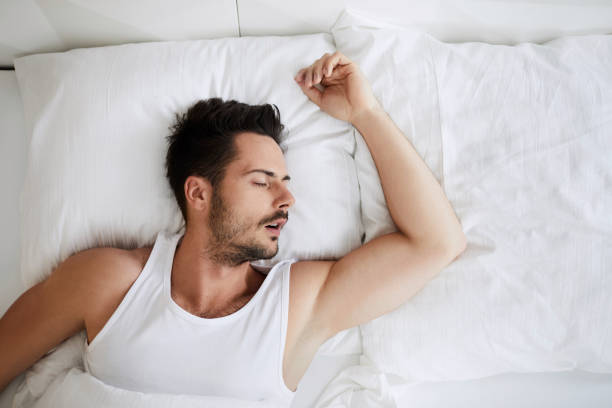 Top view of young attractive man sleeping with mouth open stock photo