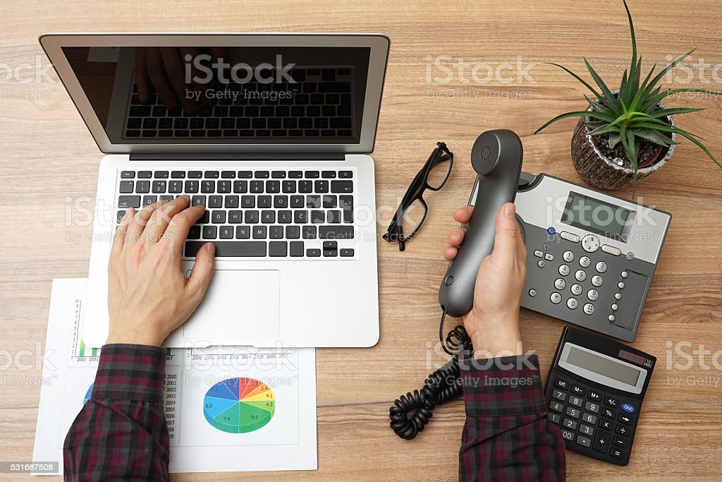 top view of young businessman working on laptop  and calling stock photo