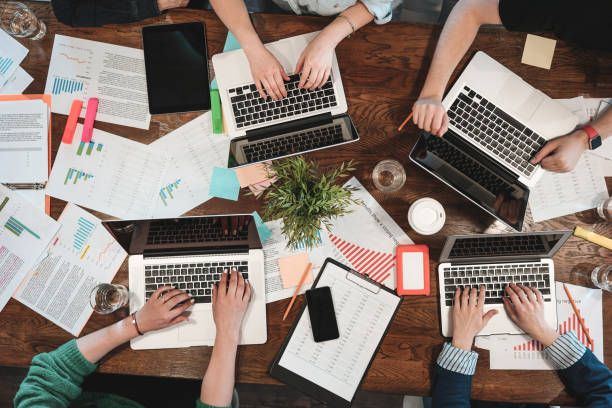 Draufsicht der coworking Jugendliche arbeiten an Laptops und Papierdokumente. Gruppe von College-Studenten mit Laptop Tisch sitzend. Team von hipster machen neues große Startup. Konzept – Foto