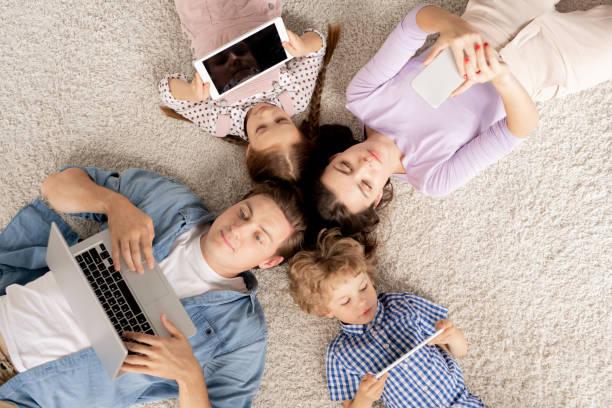 Vista superior de la familia joven tumbada en el suelo y el desplazamiento en aparatos móviles - foto de stock