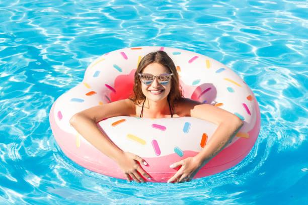 draufsicht der jungen weiblichen mit rosa kreis im pool schwimmen - pool rund stock-fotos und bilder