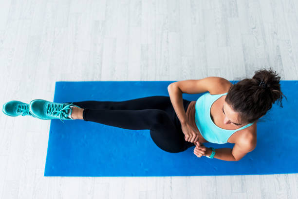 top view of young fit woman working-out doing bicycle crunches on blue mat indoors. - peso mosca foto e immagini stock